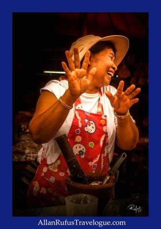 A lady laughing while making Papaya salad