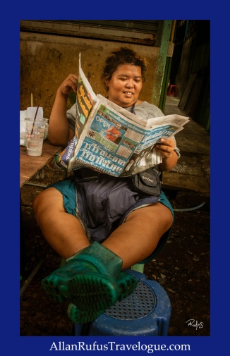 Thai lady reading the newspaper