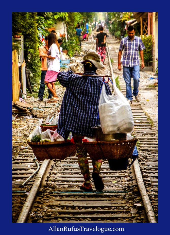Lady vendor walking along  a railway track