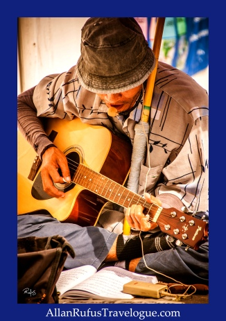 Street Photography - A street busker singing and playing the guitar!
